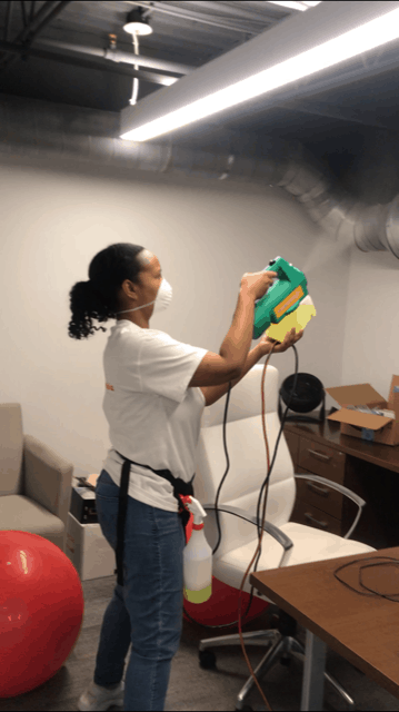 african American women sanitizing a room with a fogger