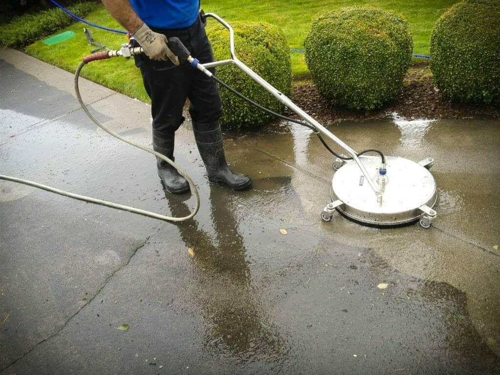 man pressure washing outdoor sidewalk with pressure washing machine