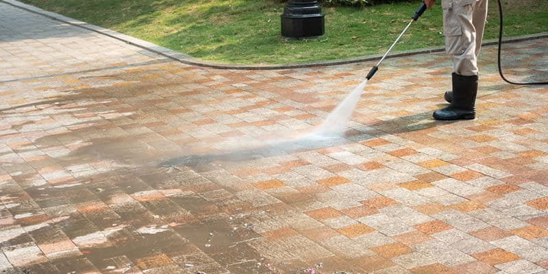 man wearing rubber boots and pressure washing driveway