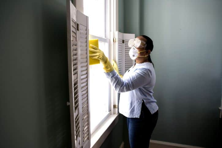 expert cleaning maid using sponge to remove dust and particles from the window