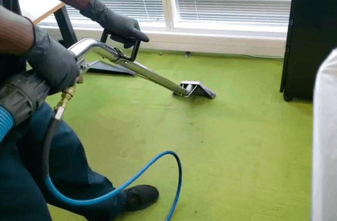black male cleaning a green carpet with a cleaning wand