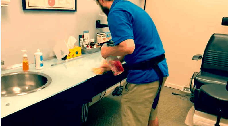 janitor cleaning countertop in office