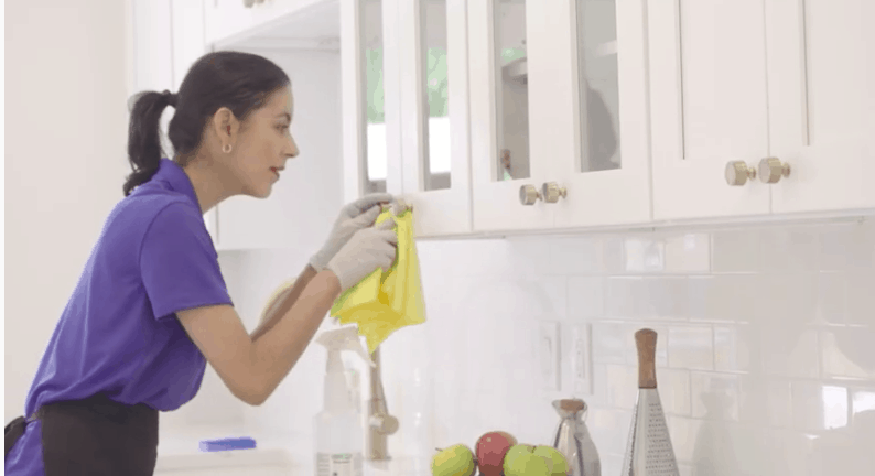 maid house cleaning a kitchen cabinet while standing on a step ladder