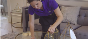 maid cleaning and dusting glass table