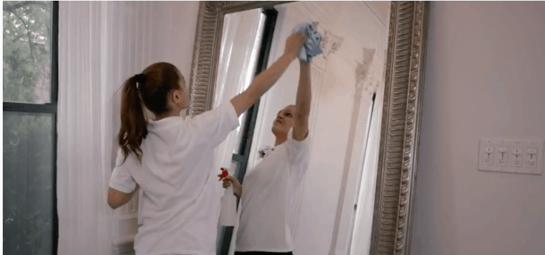 maid house cleaning and cleaning a large mirror