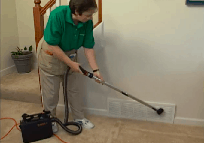 maid cleaning baseboards with a vacuum