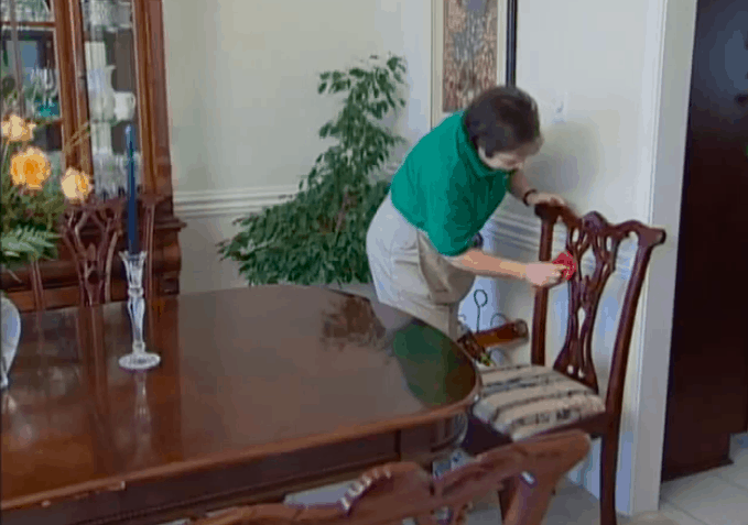 maid cleaning wood chair in dining room