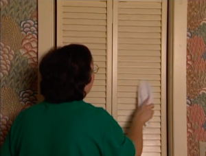 white female wiping closet door to remove dust and dirt