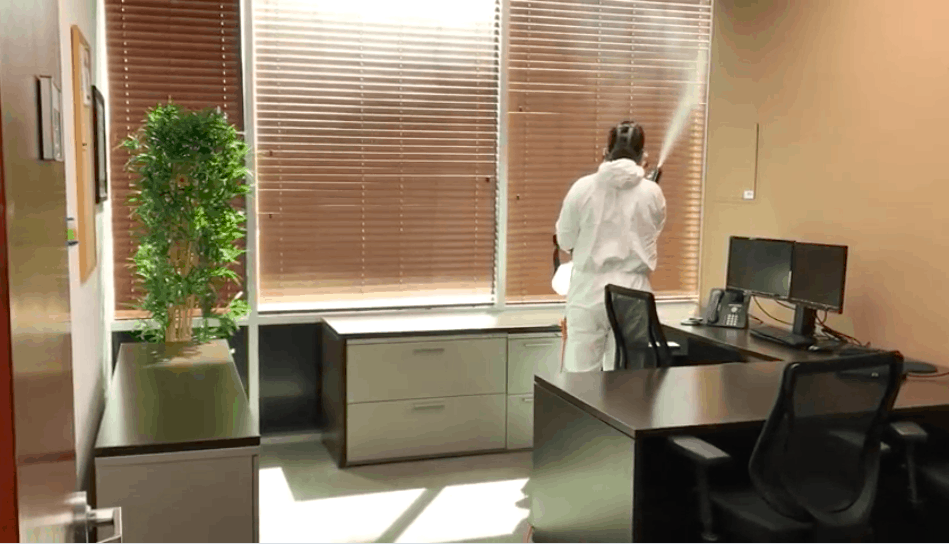 white male in hazmat suit spraying mist of disinfectant chemical in the air and surfaces