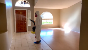white males spraying sanitizing spray in foyer of home