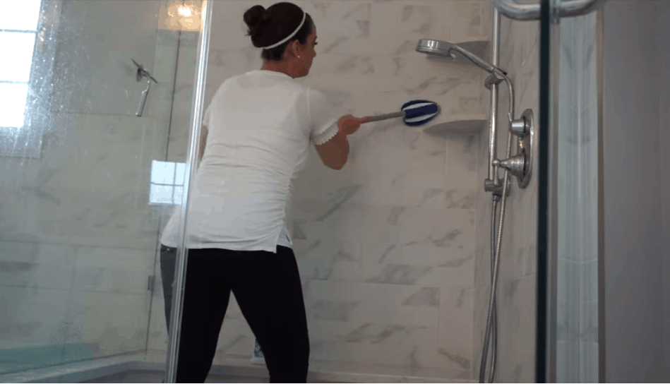 maid cleaning shower and scrubbing the shower wall
