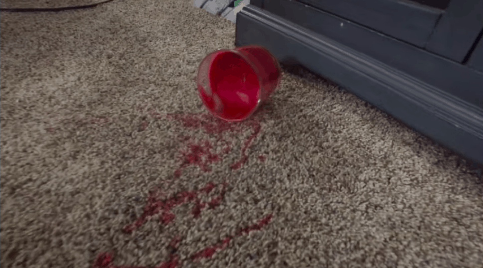 Red candle wax spilled on beige color carpet