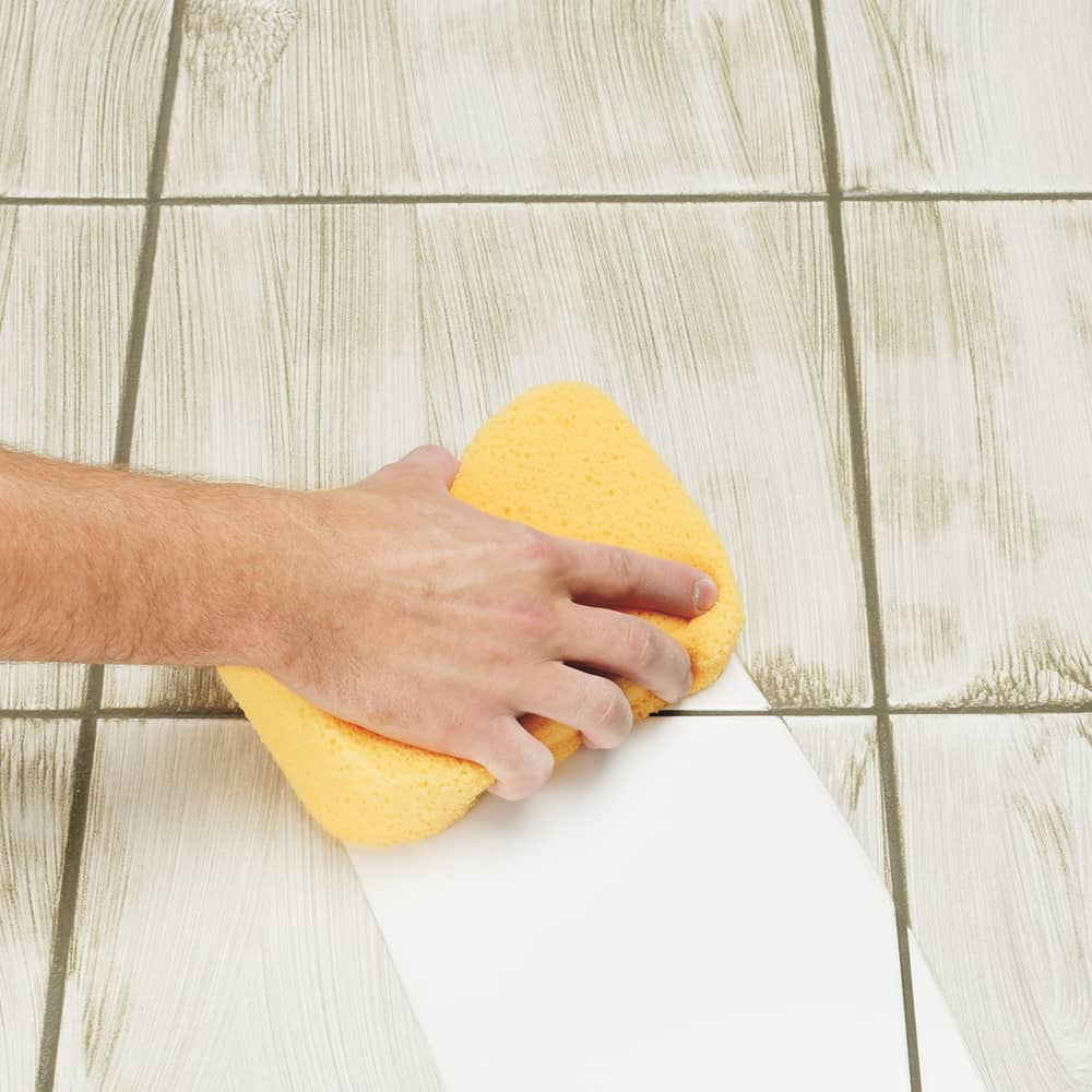 wipe dirty tile floor with yellow sponge