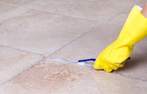 person cleaning grout with brush