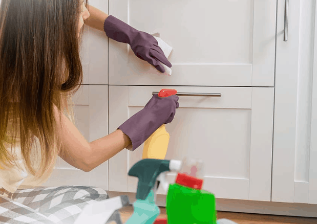 a young woman sanitizes her cupboards and drawers using various cleaning agents.
