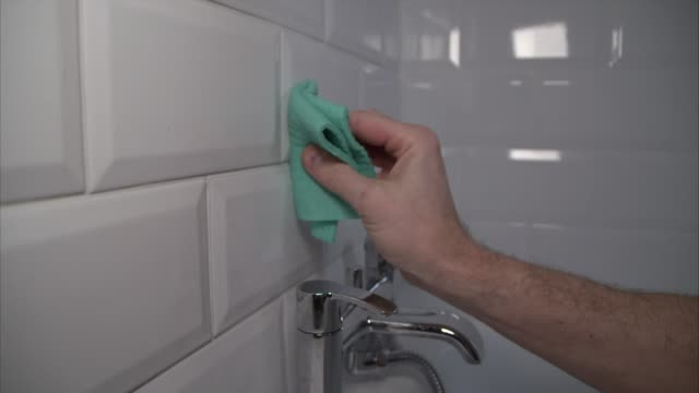 wiping tile wall with green microfiber cloth