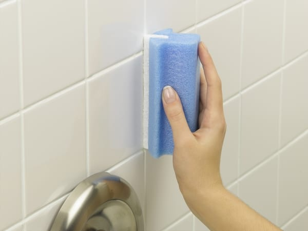 hand holding blue sponge of white tile