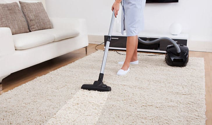 a maid cleaning solution soaked carpet using an industrial vacuum.
