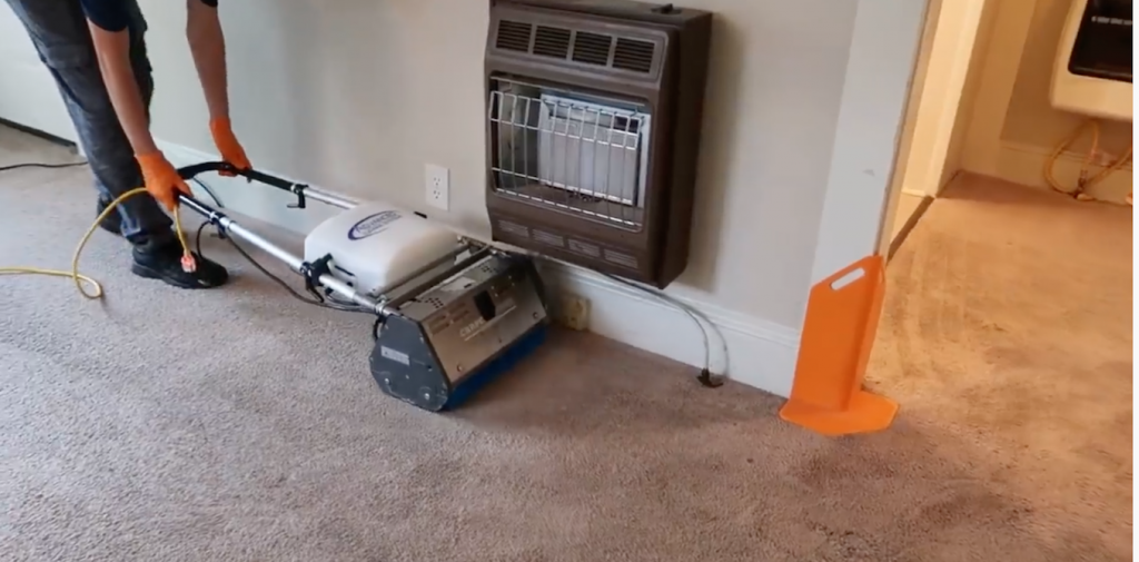 cleaner cleaning the carpet under a air conditioner