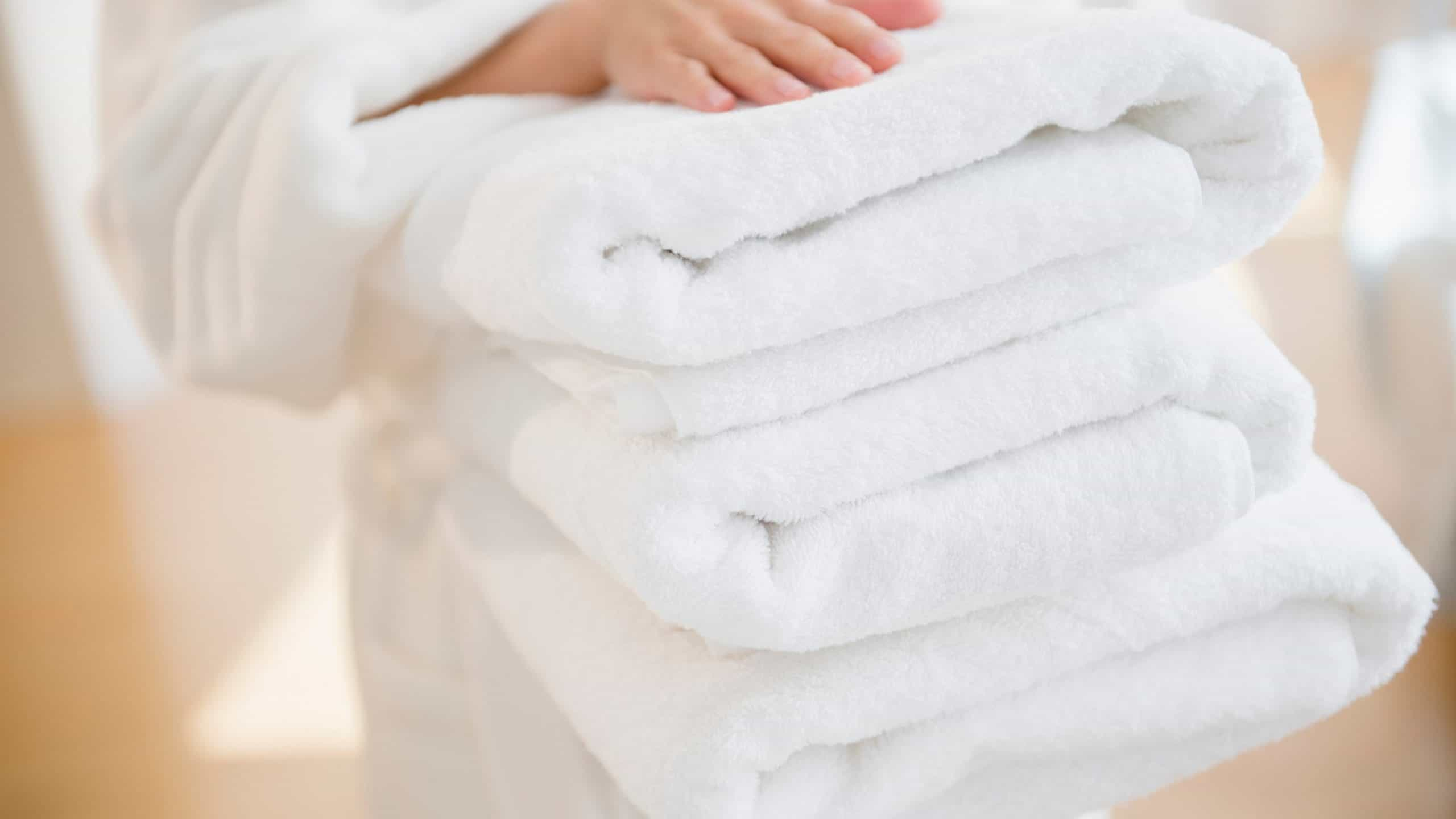 person holding 3 fluffy white towels