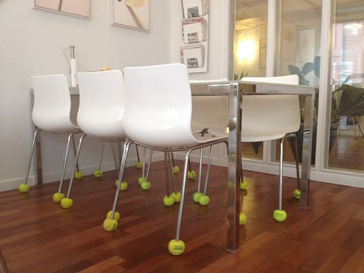 white chairs with tennis balls on the chair legs