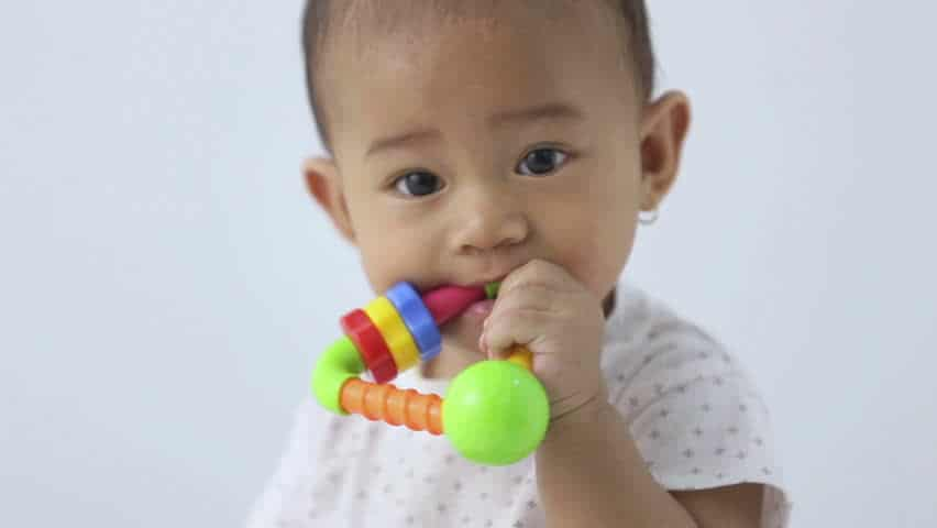asian baby with toy in his mouth