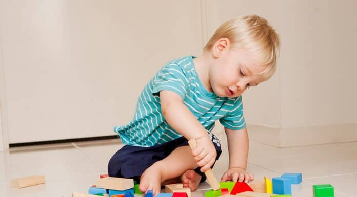toddler boy playing with color blocks