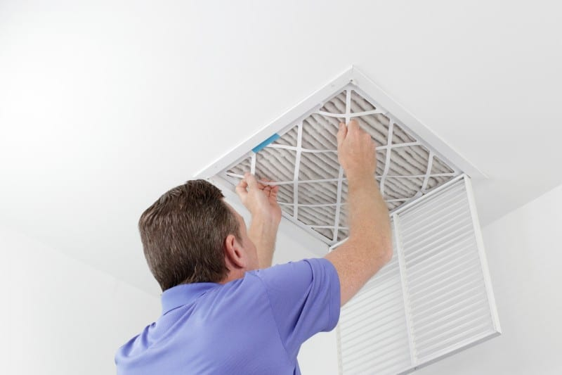 male putting air filter in ceiling vent