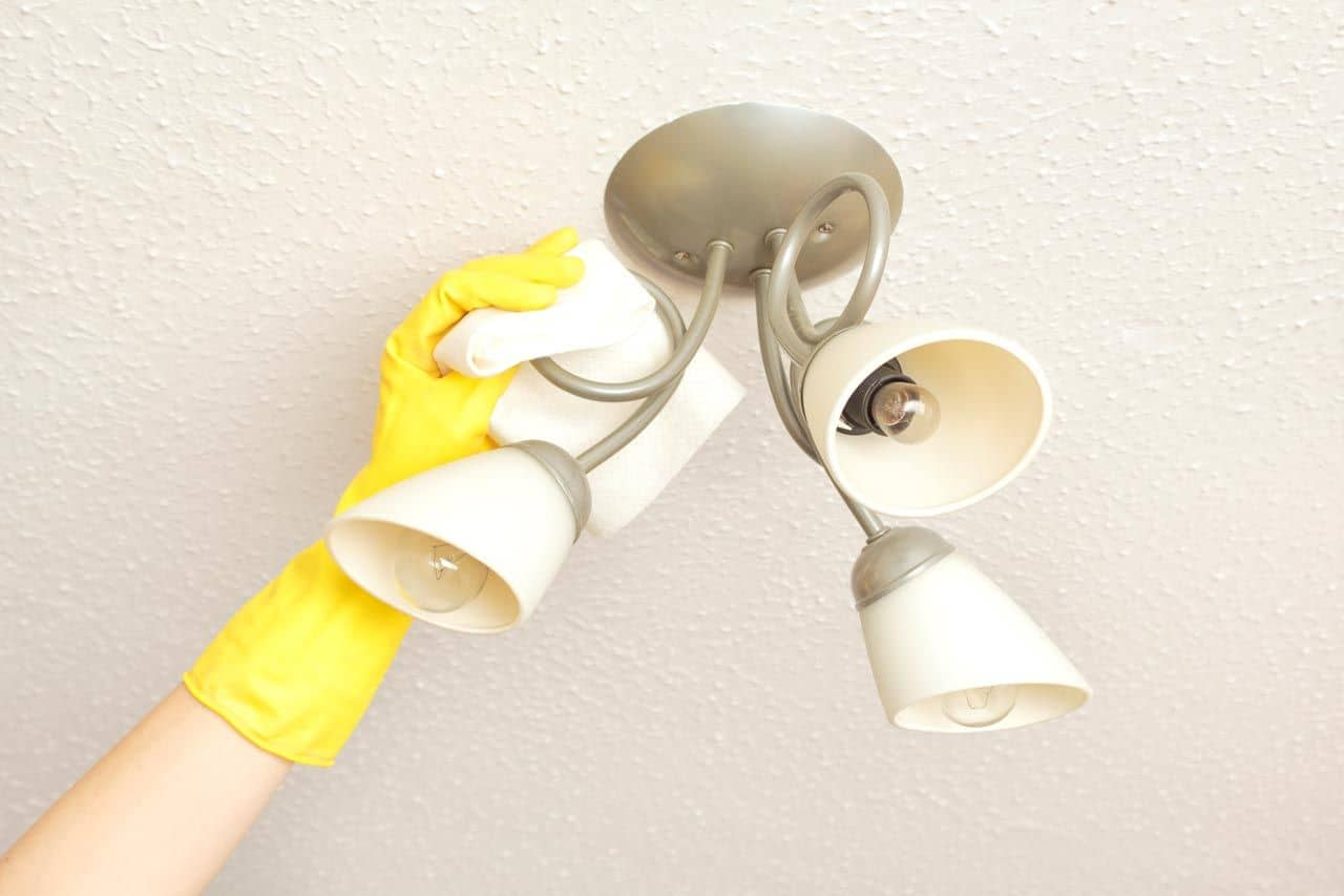 person cleaning light fixture