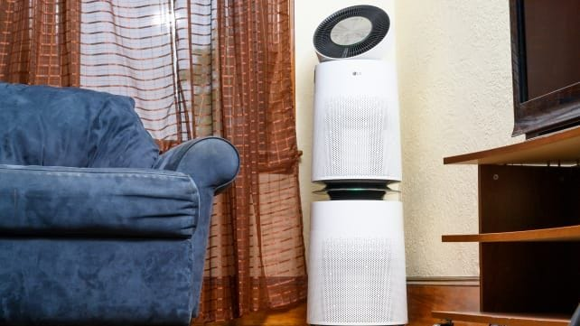 white air purifier next to blue couch