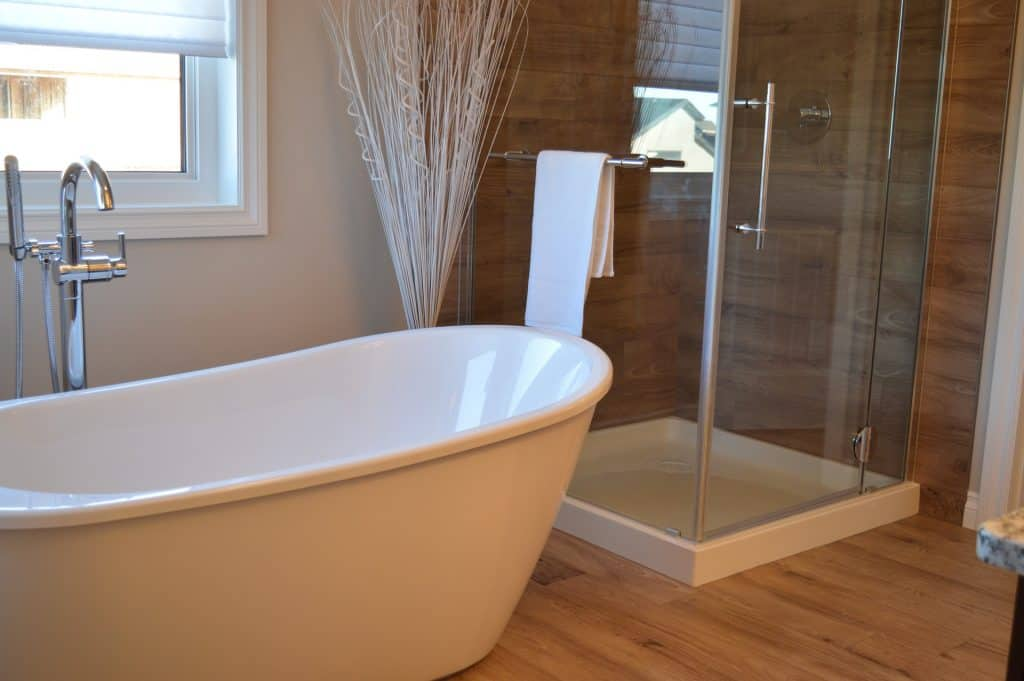 bathroom with glass shower door and tan and white bathtub