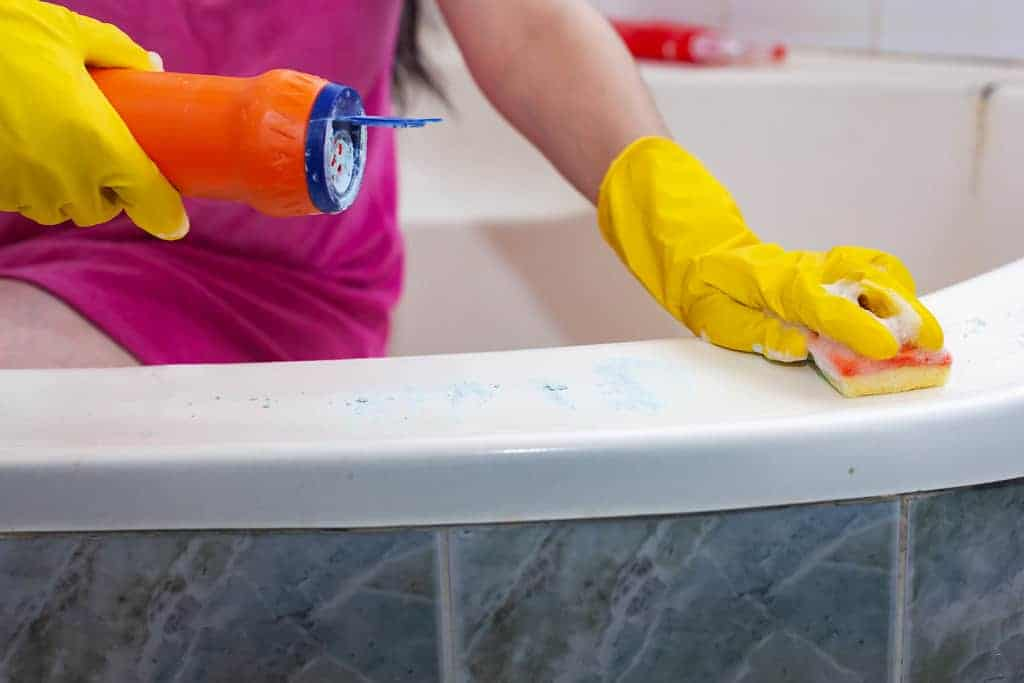 maid wearing yellow gloves cleaning a bathtub