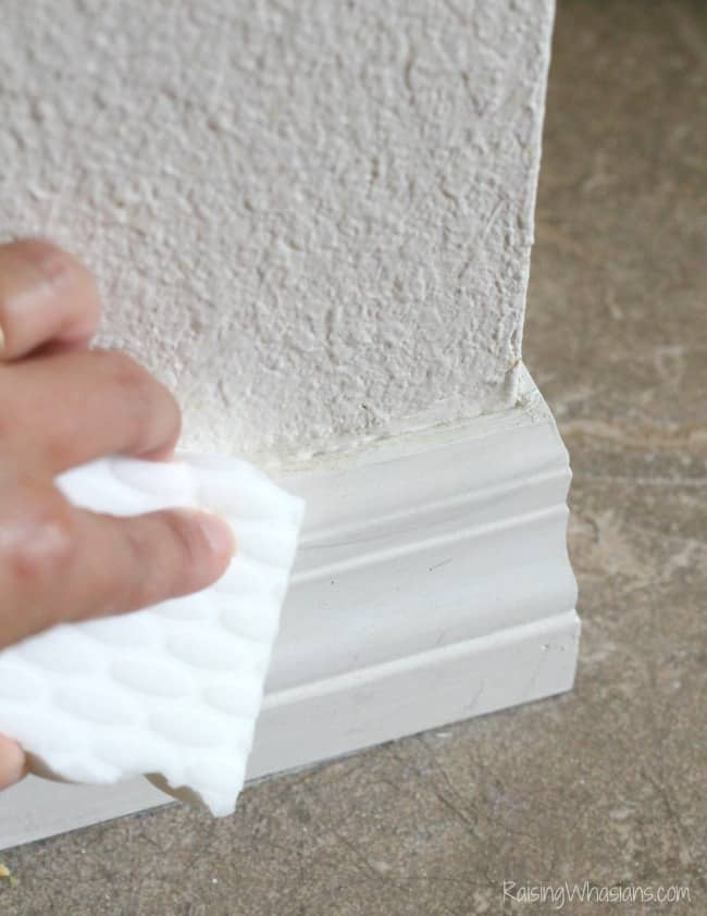 person cleaning baseboard with magic eraser