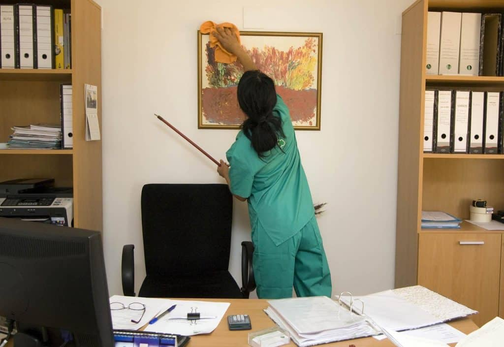janitor dusting picture Frame in office