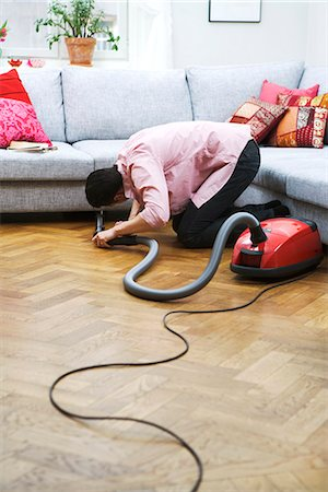 person vacuuming under couch