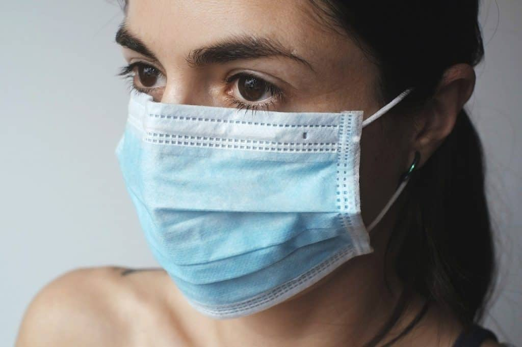 woman wearing blue surgical mask