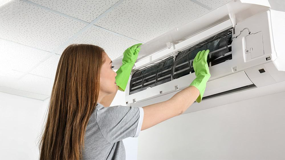 girl cleaning split unit air conditioner