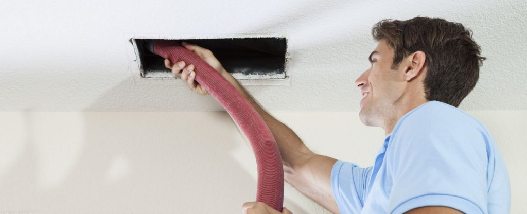 male cleaning the inside of an air duct