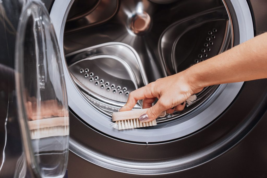 person cleaning the inside of a washing machine