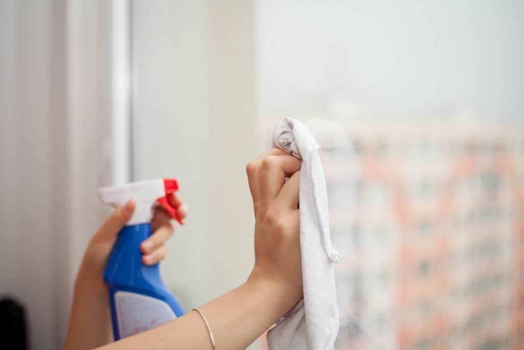 person cleaning glass while holding a towel and glass cleaner