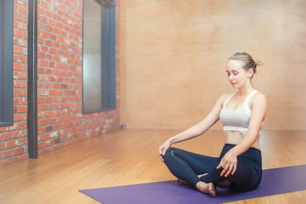 woman meditating on purple yoga mat
